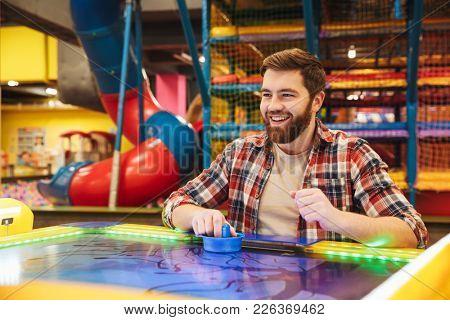 Cheerful young man playing air hockey at Arcade centre