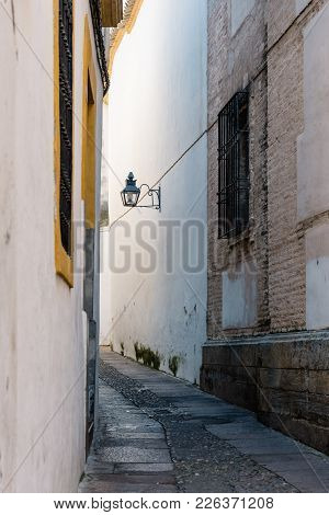 Old Typical Narrow Street In The Jewish Quarter Of Cordoba With Old Buildings With White Walls