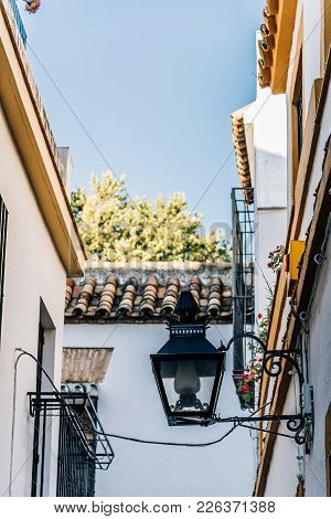 Streetlight In Old Typical Narrow Street In The Jewish Quarter Of Cordoba With Old Buildings With Wh