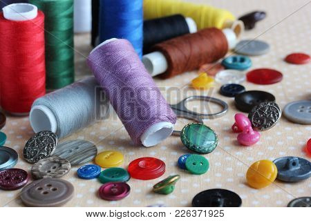Objects For Needlework And Sewing: Different Plastic Buttons, Colored Thread And Scissors On The Tab