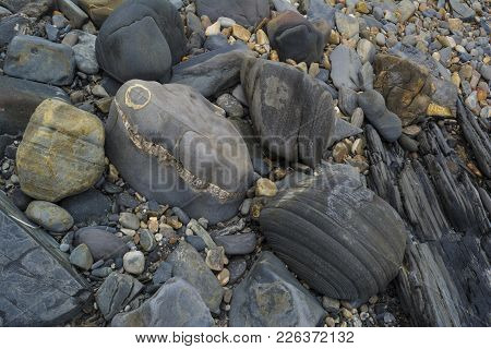 Abstract Shapes And Patterns: Dark Stones And Colourful Pebbles At Beach