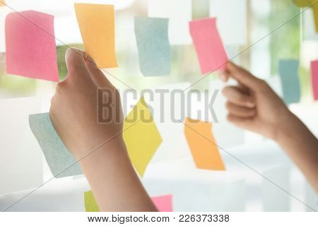 Creative Business People Reading Sticky Notes On Glass Wall With Colleague Working Use Post It Notes