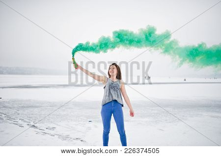 Young Girl With Green Colored Smoke Bomb In Hand In Winter Day.
