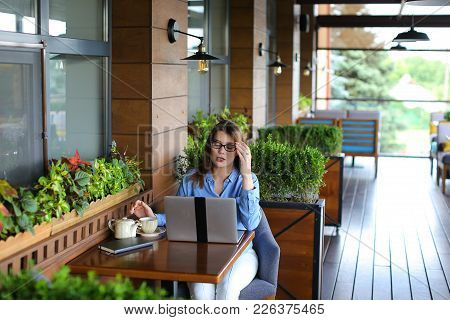 Close Up Face Of Satisfied Customer Browsing And Enjoying Social Networks At Restaurant  . Happy Gir