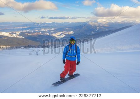 Snowboarder Posing Before A Descent In The Winter Mountains, On The Background Of Blue Sky At Sunny