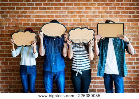 Young adults holding up copyspace placard thought bubbles