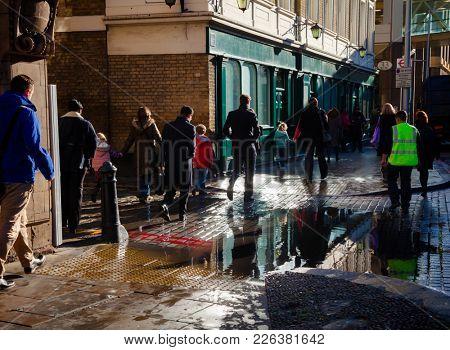 LONDON, UK - NOV 1, 2012: Pedestrians walking along wet Tooley Street near London City Hall after the rain