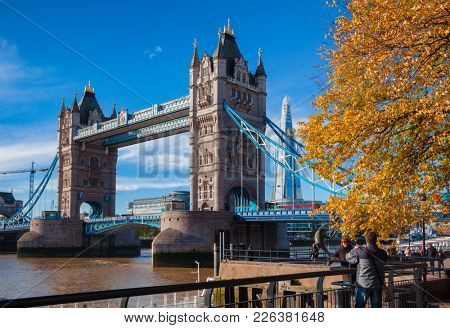 LONDON, UK - NOV 1, 2012: Tourists take  photographs in front of the Tower Bridge and Shard Skyscraper on a sunny autumn day
