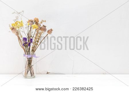 Dried Flowers And Poppy Heads In A Glass Jar On White Cracked Wall Background.