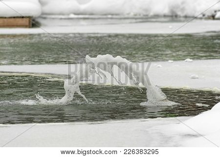 Similarity Ejaculation From Phalo. Fountain In The Snow, Cold Water Beats From The Icy Nozzle. Aroun