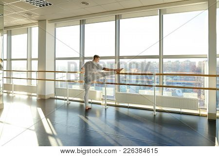 Gymnast Train Near Ballet Barre In Sport Gym, Guy Diligently Doing Stretching Exercises For Legs. Ta