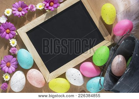 Easter Eggs And A Chalkboard With Flowers - Easter Banner With A Rustic Bucket Full Of Painted Eggs