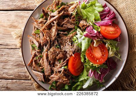 Pulled Spicy Beef With Fresh Vegetables Close-up On A Table. Horizontal Top View From Above