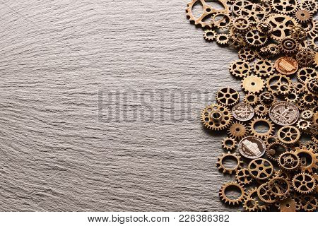 Various metal cogwheels and gear wheels with USA coins over slate background