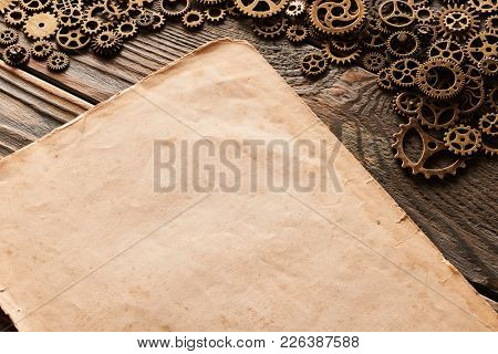 Various metal cogwheels and gear wheels with blank paper sheet over wooden background