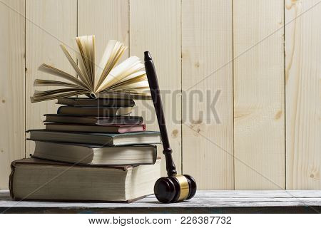 Legal Law Concept - Open Law Book With A Wooden Judges Gavel On Table In A Courtroom Or Law Enforcem