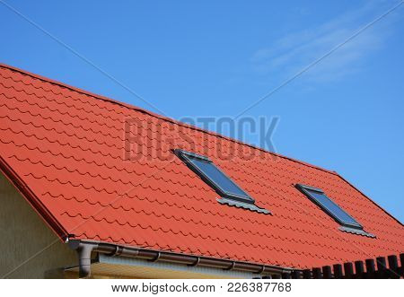 Close Up On Skylight Attic Windows With Red Metal House Roof. Modern Home Attic Skylight Waterproofi