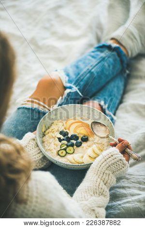Healthy Winter Breakfast In Bed. Woman In Woolen Sweater And Shabby Jeans Eating Vegan Almond Milk O