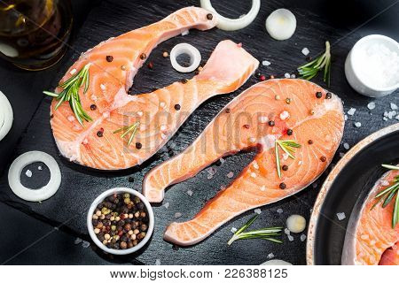 Fresh Raw Unprepared Fish Salmon Or Trout, Steaks, In A Skillet For Cooking, With Salt, Pepper On Bl