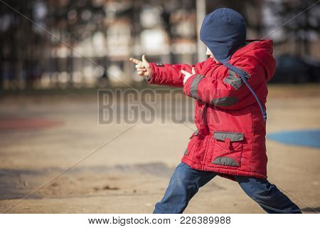 Little Cute Toddler Boy Running Around In The Park, Playful And Cheerful, Wearing A Red Jacket