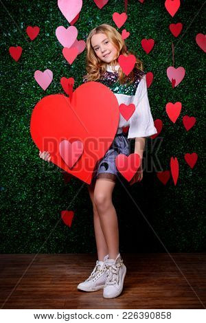 Full length portrait of a pre-teen girl holding red heart surrounded by hearts over lawny background. First love. Valentine's Day.