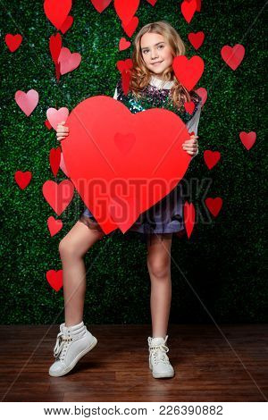 Full length portrait of a pre-teen girl poses surrounded by hearts over lawny background. First love. Valentine's Day.