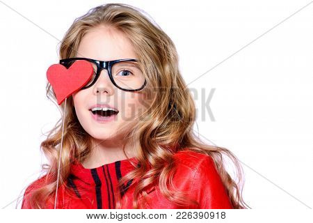 Pretty ten-year-old girl covered one eye with a heart on a stick. Isolated over white. First love. Valentine's Day.