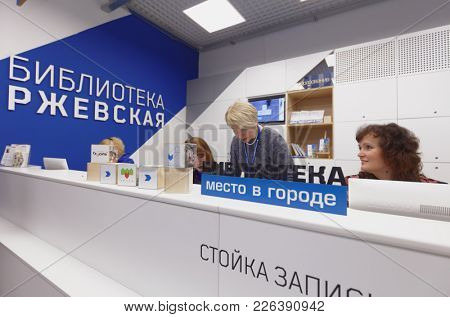 ST. PETERSBURG, RUSSIA - NOVEMBER 24, 2017: Staff at the service desk of the municipal library Rzhevskaya in the day of it opening after renovation. The library was equipped with new technologies