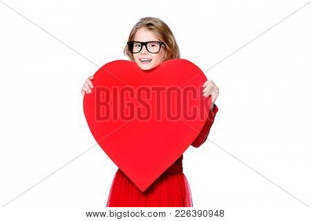 Portrait of a pretty pre-teen girl holding big red heart. Isolated over white. First love. Valentine's Day.