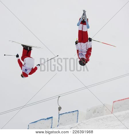 KRASNOE OZERO, LENINGRAD REGION, RUSSIA - FEBRUARY 1, 2018: Nikita Parkachev (14) and Ilya Chevskiy, both of Russia, compete in dual mogul during Freestyle Europa Cup competitions. Chevskiy won bronze
