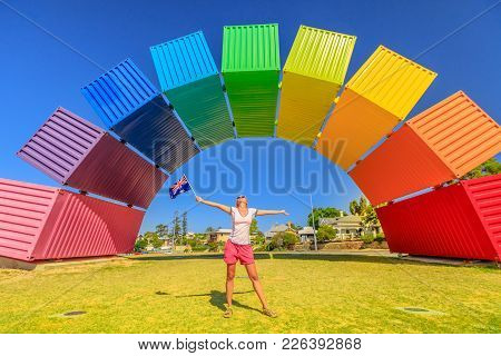 Australia Travel Welcome. Happy Woman With Australian Flag Waving Enjoys Rainbow Sea Container. Frem