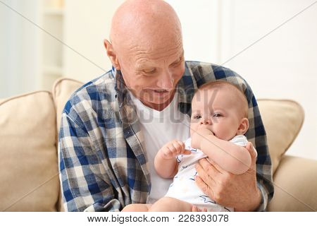 Senior man playing with his little grandchild at home