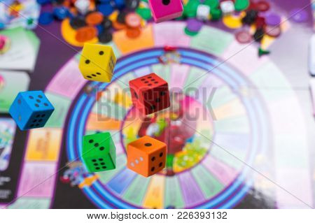 Several Rolling Color Dice Fall On A Table With Board Game. Gaming Moments In Dynamics. Copy Space