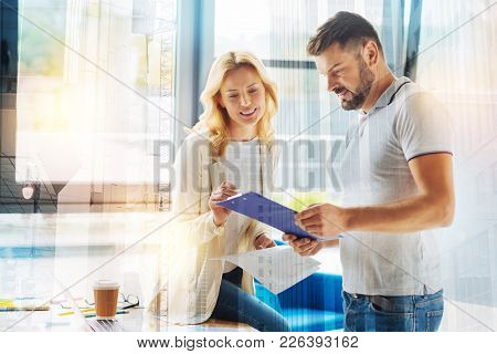 Helpful Coworker. Positive Friendly Young Woman Sitting Comfortably On The Table And Smiling While L