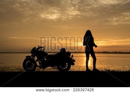 Beautiful Woman Biker Enjoying Sunset, Female Riding Motorcycle. Motorbike Driver Traveling The Worl