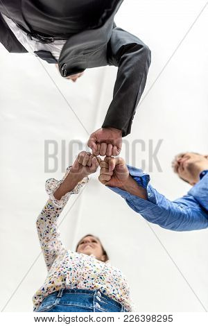 Three Business Colleagues Knocking Fists In A Motivational Gesture Of Solidarity Viewed Directly Fro