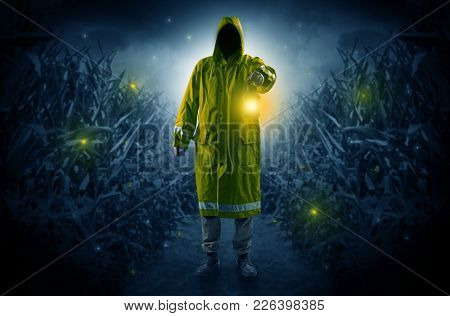 Man in raincoat at night coming from thicket and looking something with glowing lantern