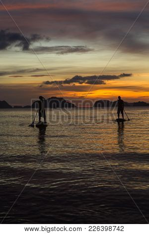 Two Man Silhouette Standing On Sup Boards On Sunset Time In El Nido, Palawan, Philippines, Corong Co
