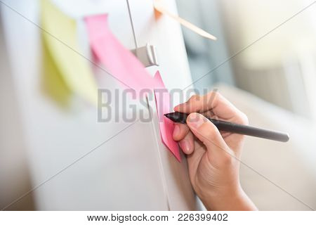 Female Hand Writing On Post It Notes. Sticky Note On Wall. Colorful.