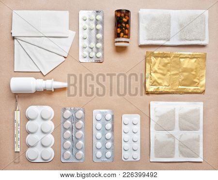 Pills, Thermometer, Nose Drops, Powders And Handkerchiefs For Flu Treatment On Kraft Paper Backgroun