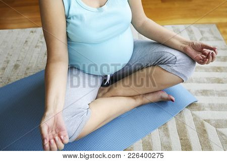 Close Up Of Pregnant Woman Meditating While Sitting In Lotus Position
