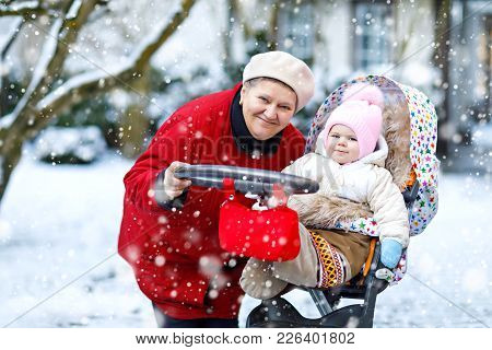 Beautiful Grandmother Walking With Baby Girl In Pram During Snowfall In Winter. Happy Family. Carefr