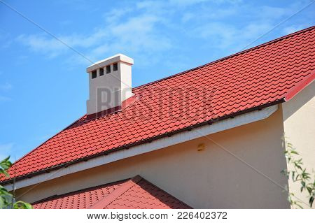 Beautiful Red Metal Roof With Roof Gutter, Fascia, Ventilation And Chimney. House Roofing Constructi