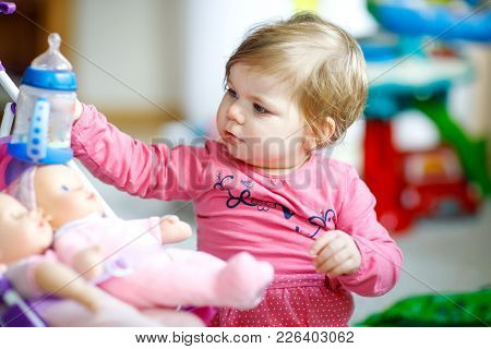 Adorable Cute Beautiful Little Baby Girl Playing With Toy Doll And Drinking Water Or Milk From Bottl