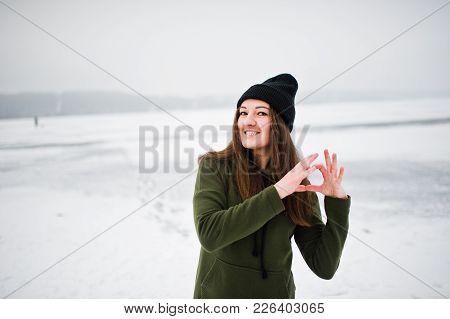 Funny Girl Wear On Long Green Sweatshirt, Jeans And Black Headwear, At Frozen Lake In Winter Day, Sh