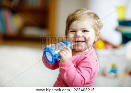 Cute Adorable Baby Girl Holding Nursing Bottle And Drinking Formula Milk Or Water. First Food For Ba