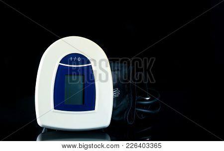 Blue-white Digital Blood Pressure Monitor With Wide Range Cuff Isolated On Dark Background. Health C