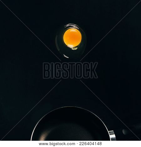 Close Up View Of Raw Egg Yolk Falling On Frying Pan Isolated On Black
