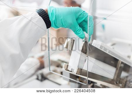 Hand Placing Labels Into A Label Inserting Machine. The Machine Puts Labels Inside Medicine Packagin