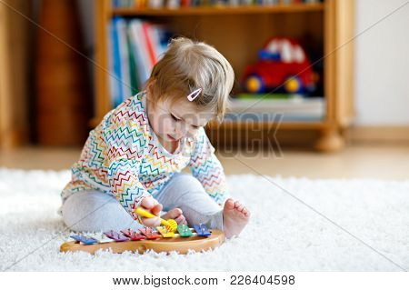 Adorable Cute Beautiful Little Baby Girl Playing With Educational Wooden Music Toys At Home Or Nurse